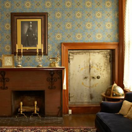 Blue papered walls, fireplace with candlesticks on the mantel and small heavy door leading to a safe room