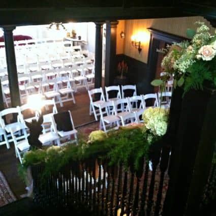 View from a greenery and floral covered balcony of rows of white chairs set up for a wedding