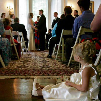 People sitting in white chairs in a room with hardwood floors watching a bride and groom get married
