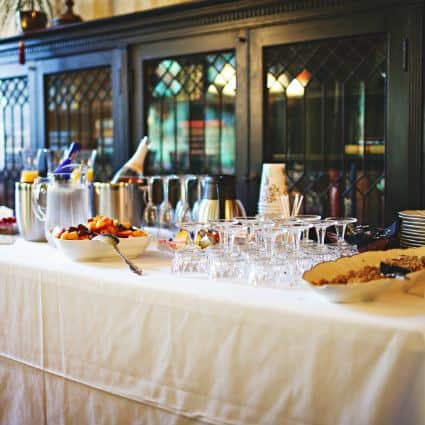 White covered table topped with wine glasses, paper cups, fresh fruit, carafes of water, and chilled bottles