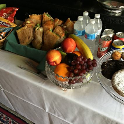 White covered table topped with water, soda, bowl of fruit, bags of chips and fresh cut sandwiches