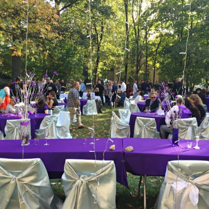 People sitting at purple covered tables and white covered chairs outside on a grassy lawn surrounded by trees