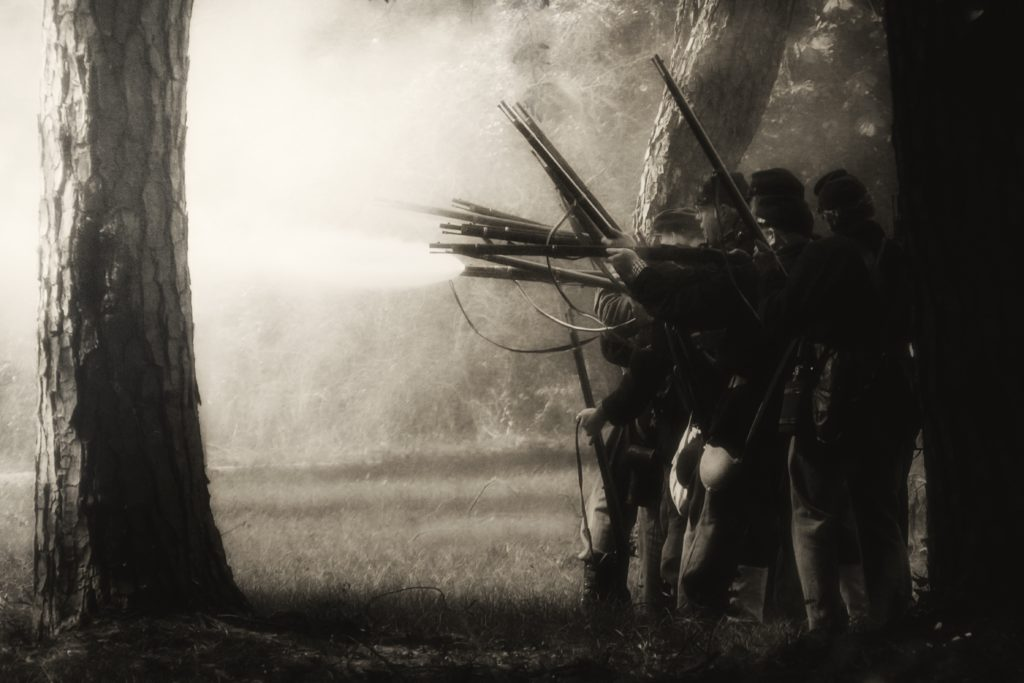 Foggy black and white photo of civil war re-enactment with entrymen with rifles bunched on right headed toward trees and battle