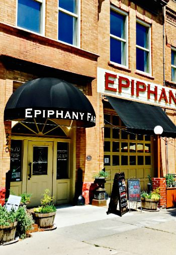 Exterior view of Epiphany Farms Restaurant, a brick building with black awnings over yellow painted doors
