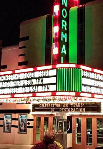 Exterior view of theatre at night with red, white and green neon signs advertising showtimes.