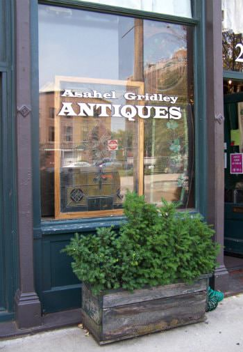 Close up exterior view of Asahel Gridley Antiques store window painted in dark teal and muted purple
