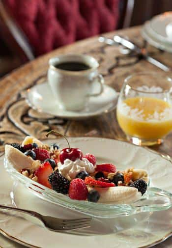 White and gold plate filled with fresh fruit and nuts, saucer and cup of coffee, and glass of orange juice