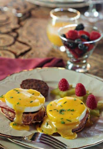 White and gold plate filled with eggs Benedict, a sausage patty, and raspberry-topped pineapple slices