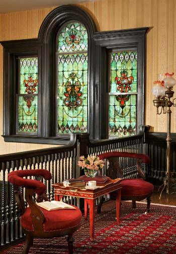 Elegant balcony with gold papered walls, stained glass windows with dark woodwork, ornamental rug with two red chairs and table
