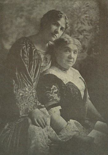 Old black and white photograph of a younger women sitting behind an older woman wearing elegant dresses