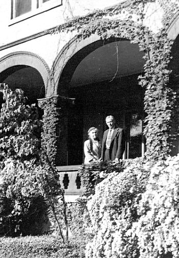 Black and white photo of an older couple standing together on a balcony with arched openings covered in ivy