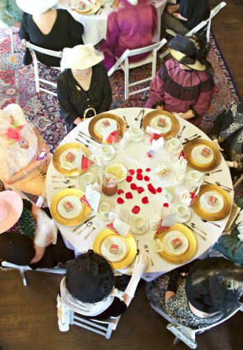 Top view of a group of elegantly dressed women in hats sitting at a white round table set for lunch