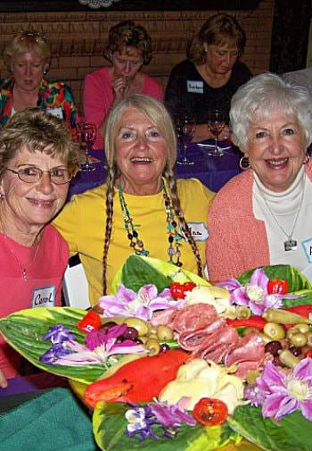Three older women in pink and yellow shirts embracing around a table of colorful appetizers and smiling