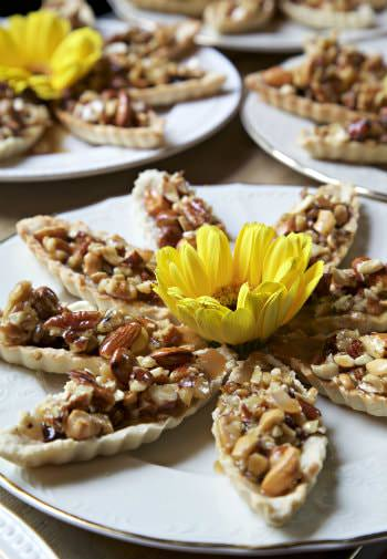 Several nut topped pastries surrounding a yellow flower on white plates edged in gold