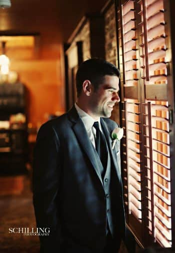 Smiling bridegroom with dark brown hair standing near a window with wood blinds and looking out