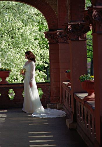 Bride in a white dress carrying flowers standing on an elaborate balcony looking back at the lush green trees