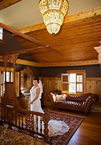 Smiling bride in white dress standing in a rustic room with wood floors and ceiling and a leather chaise lounge