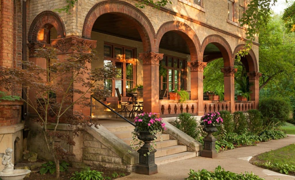 Elegant brick mansion with covered portico with arches and columns surrounded by lush greenery