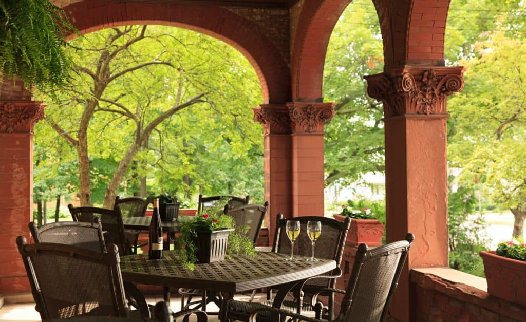 Beautiful brick red arched covered porch with black metal tables and chairs surrounded by lush greenery