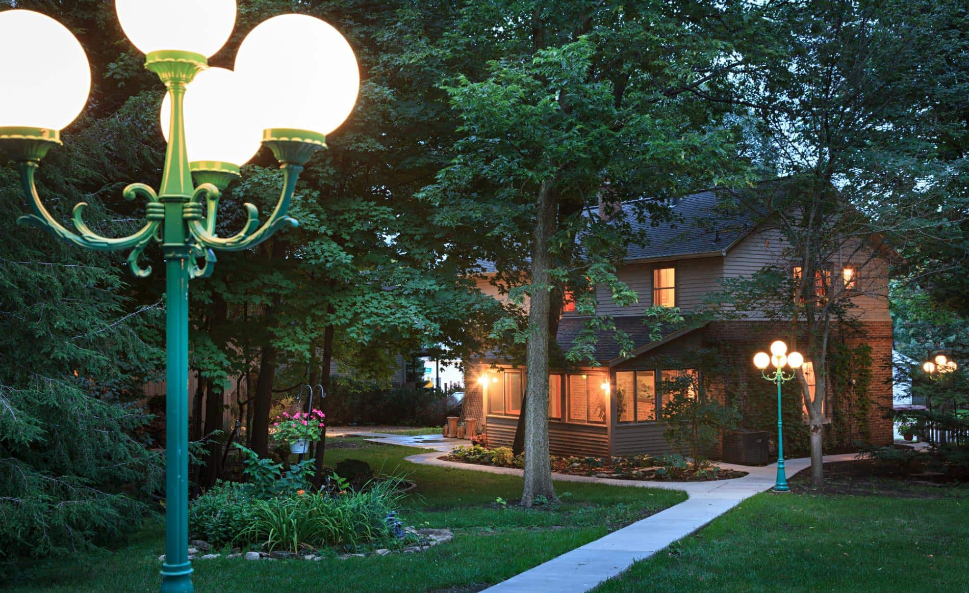 Exterior view of backyard at dusk with a sidewalk, green grass, a green light post and several trees