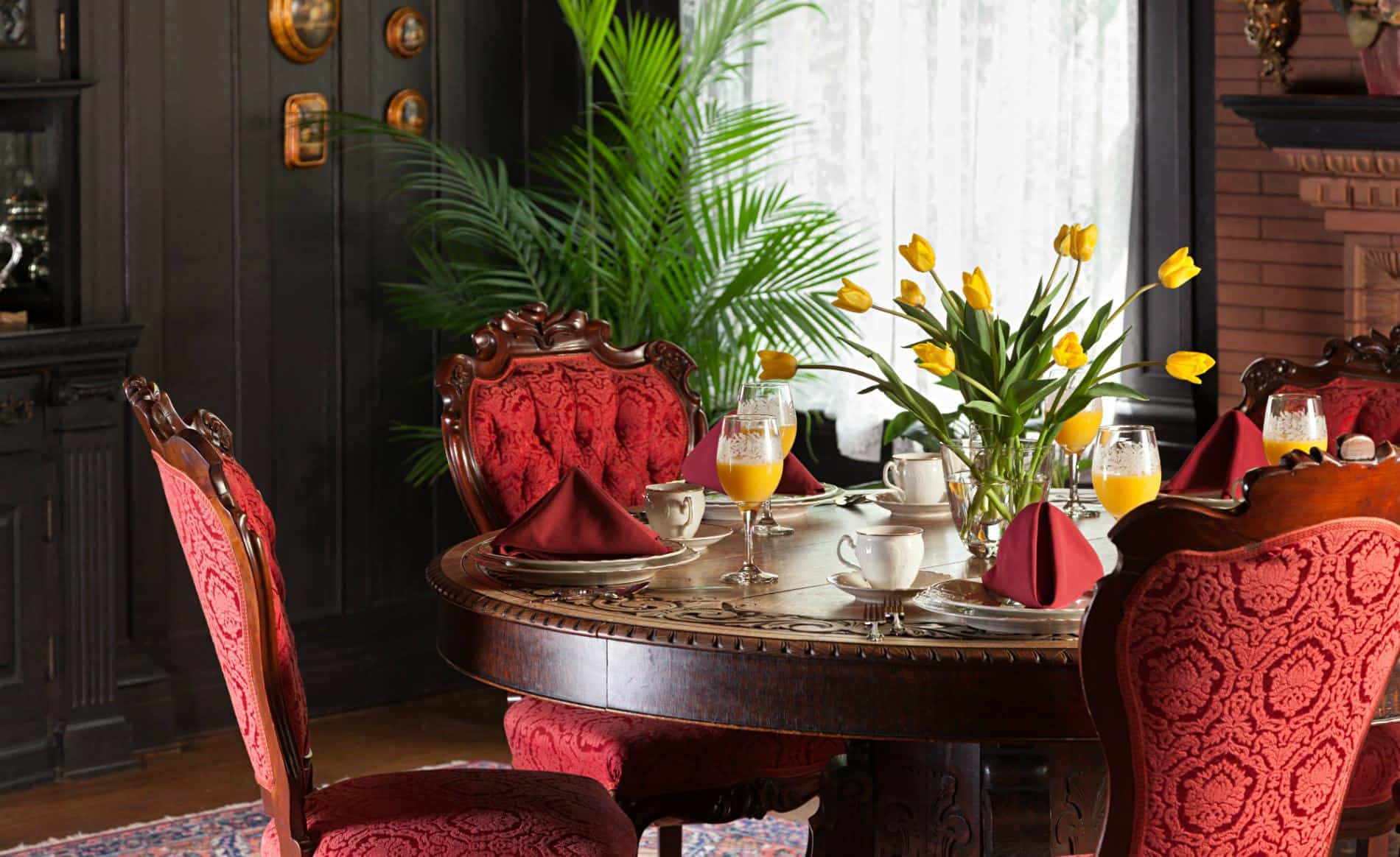 Red velvet chairs around carved wood table with white china, red napkins, orange juice in wine glasses and yellow tulips