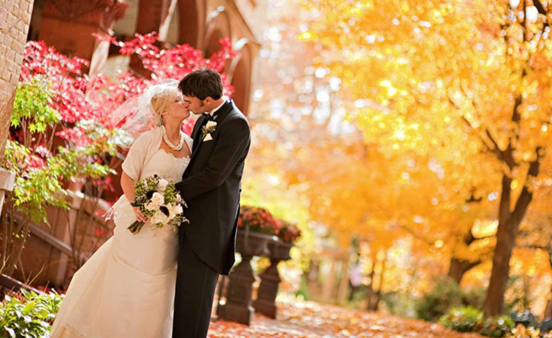 Groom kissing bride in ivory dress and veil outside the mansion surrounded by yellow, orange, red and green leafed trees