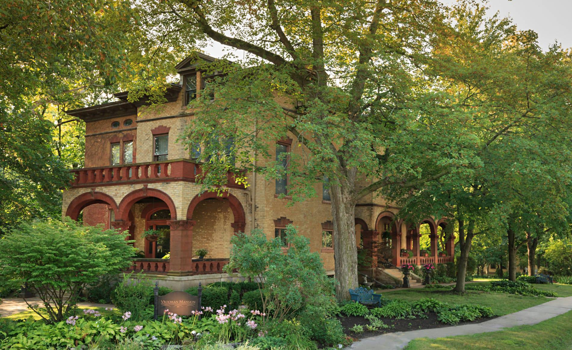 Brick mansion with red trim surrounded by lush green landscaping