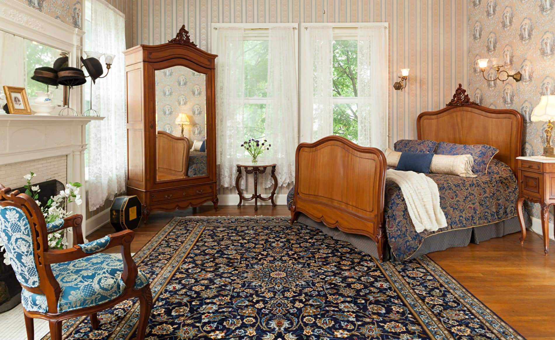 Blue and beige papered walls, wood floors, white lace curtains, wood bed, mirrored cabinet and lots of natural light