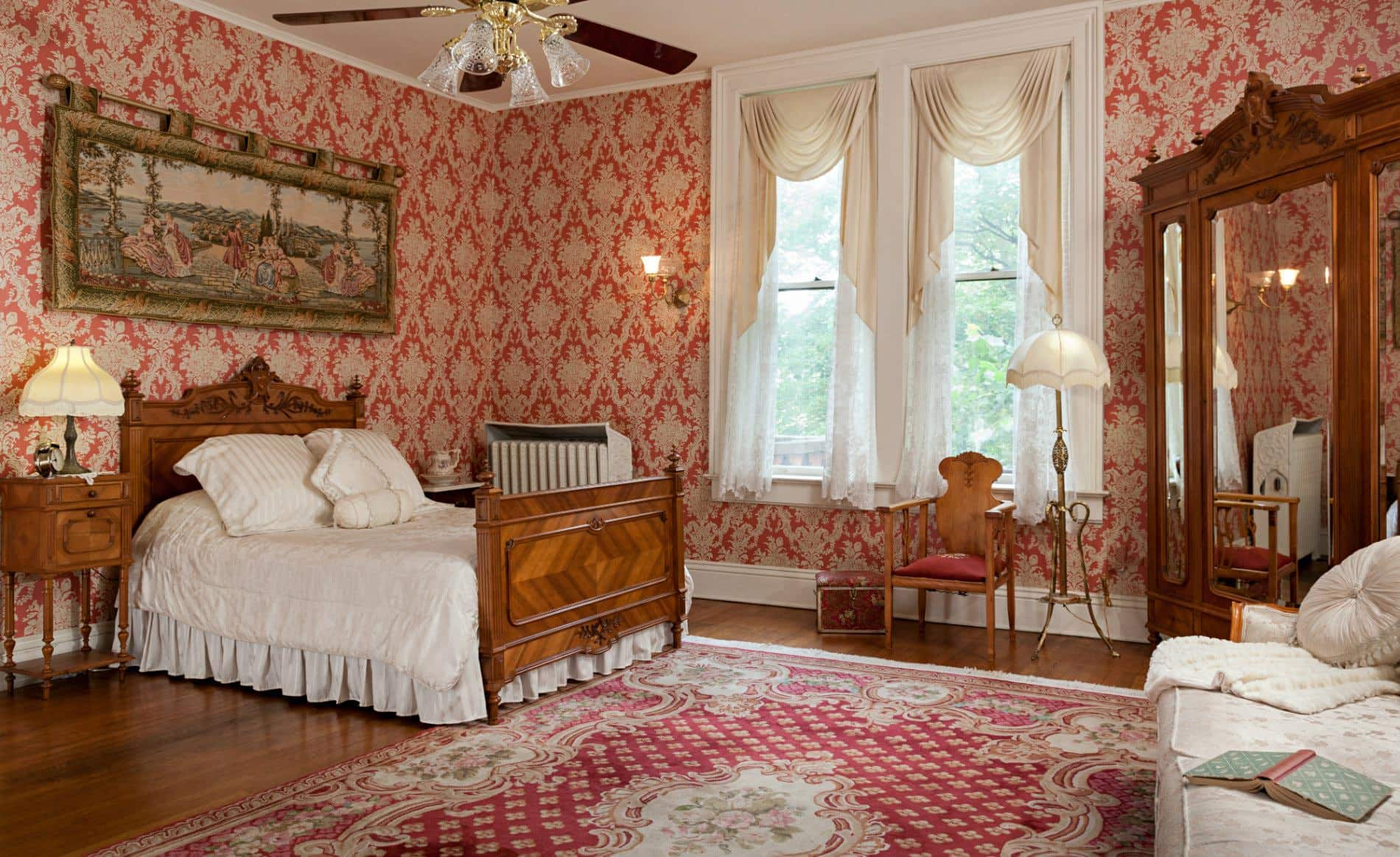 spacious room with red and white papered walls, wood floors, wood carved bed with white bedding, and large mirrored cabinet