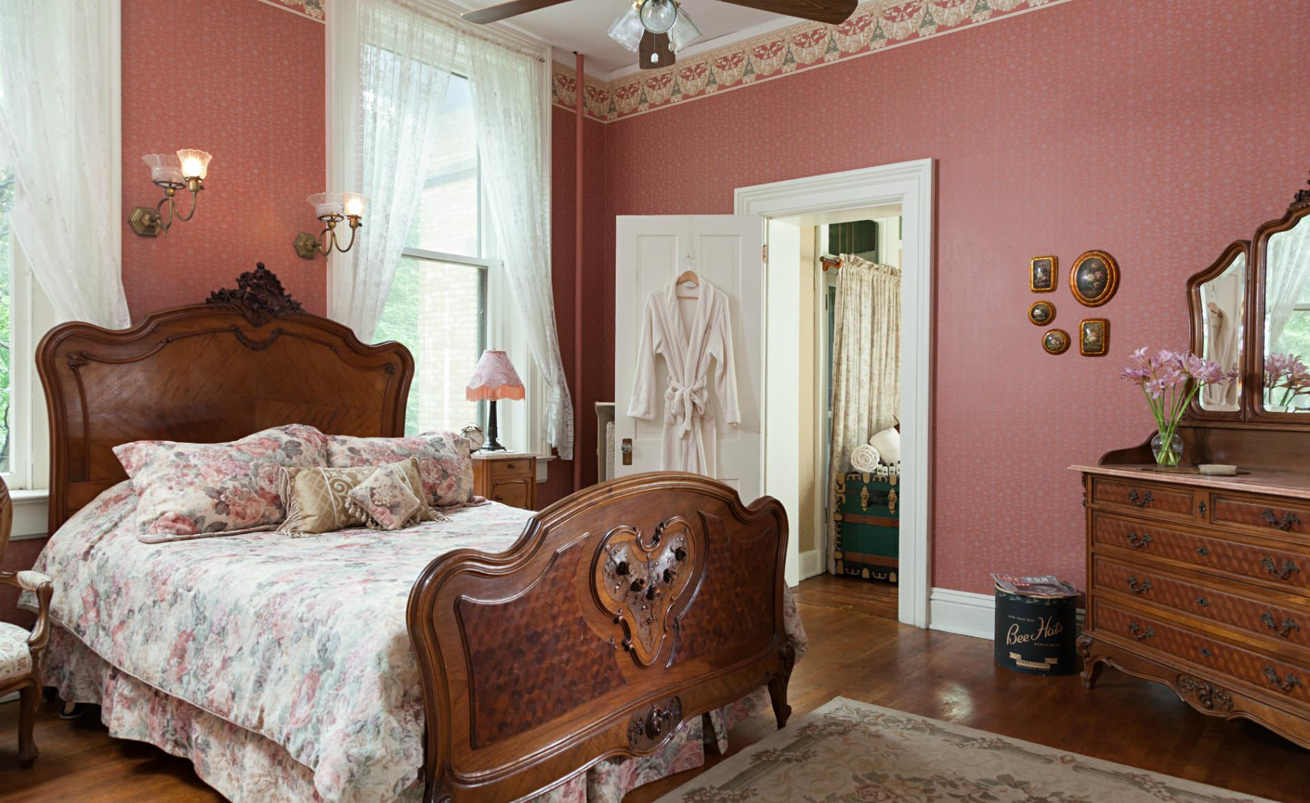 Rose papered walls, white lace curtains, white trim and doors, wood floors and elegant carved bed and dresser with mirror