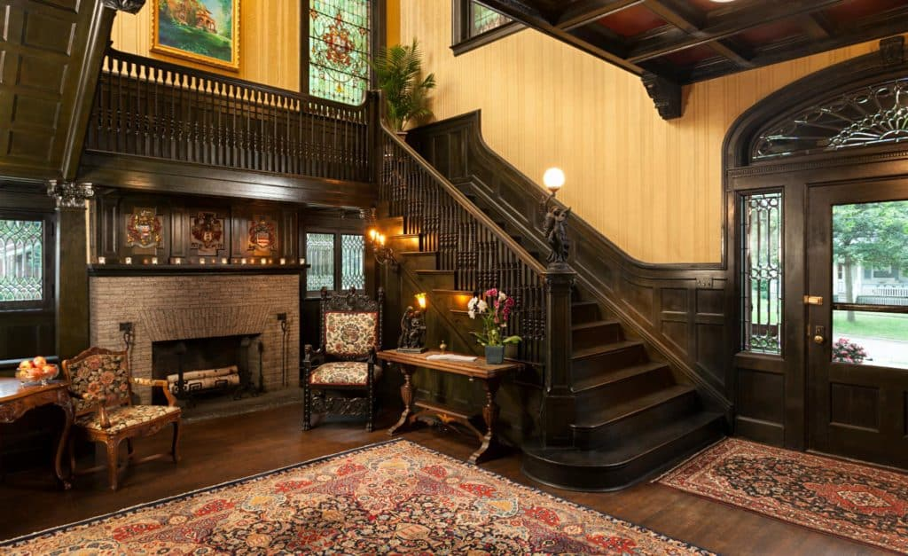 Beautiful mansion foyer with dark stained wood trim and staircase, wood floors, fireplace, and large area rug