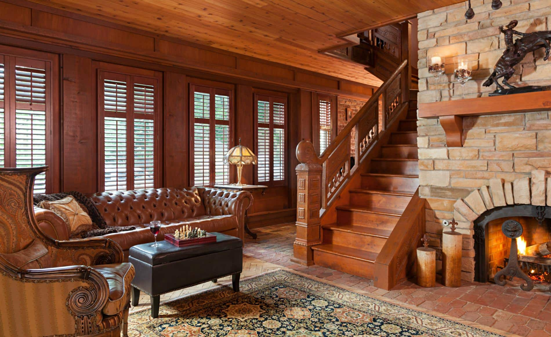 Cozy room with wood paneled ceilings, wood and brick floor, stone fireplace, leather sofa and leather ottoman with chess board