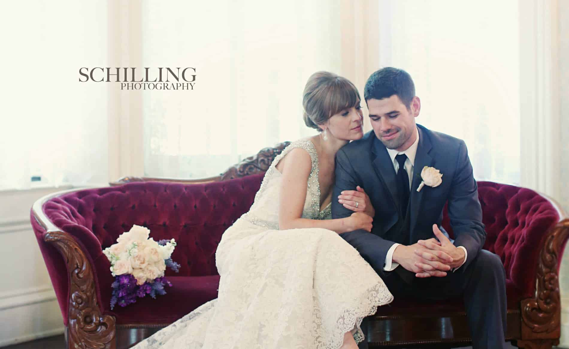 Bride in white dress hugging groom while sitting on a red velvet sofa