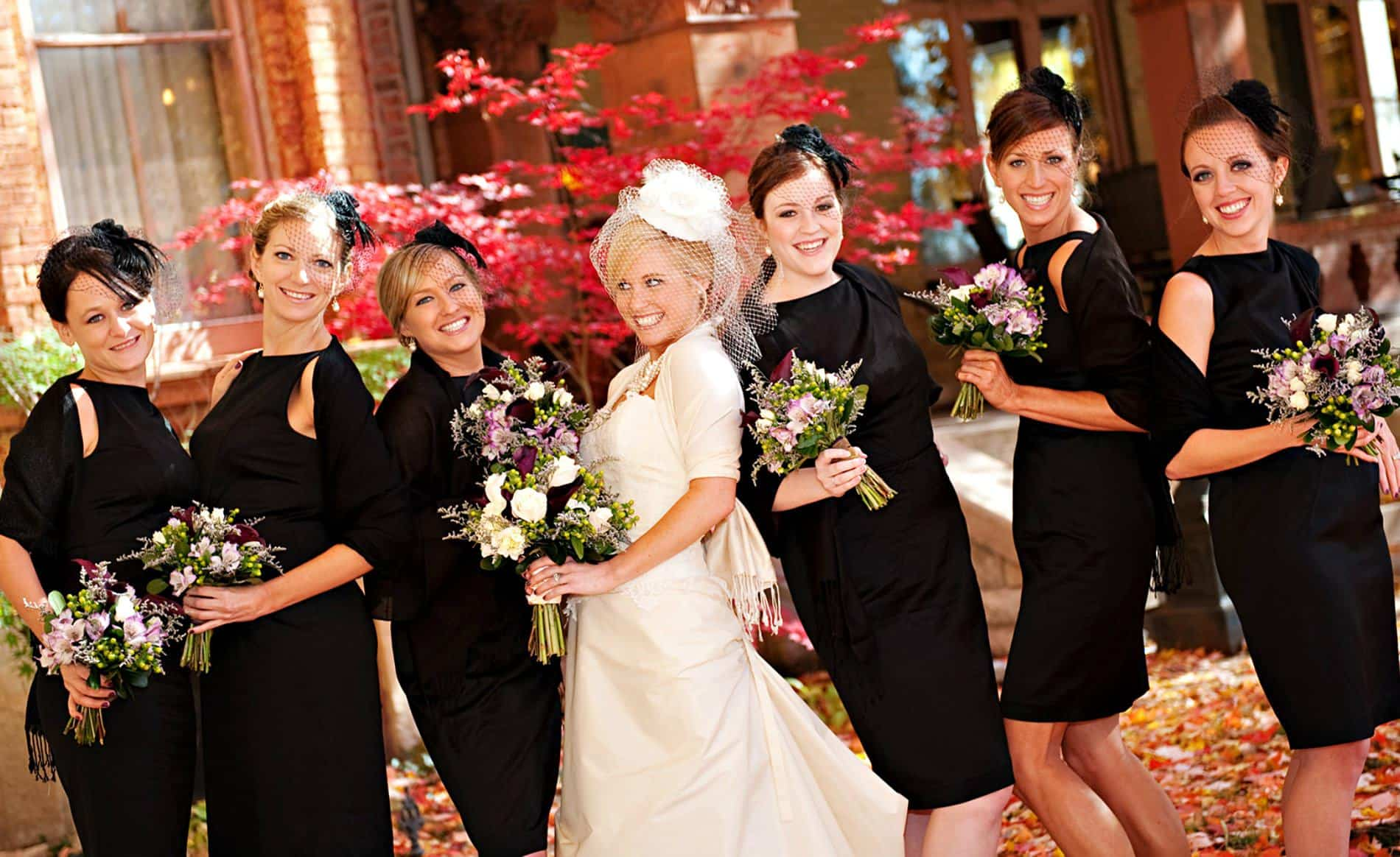 Smiling bride in white dress and veil flanked by three bridesmaids on each side wearing black dresses