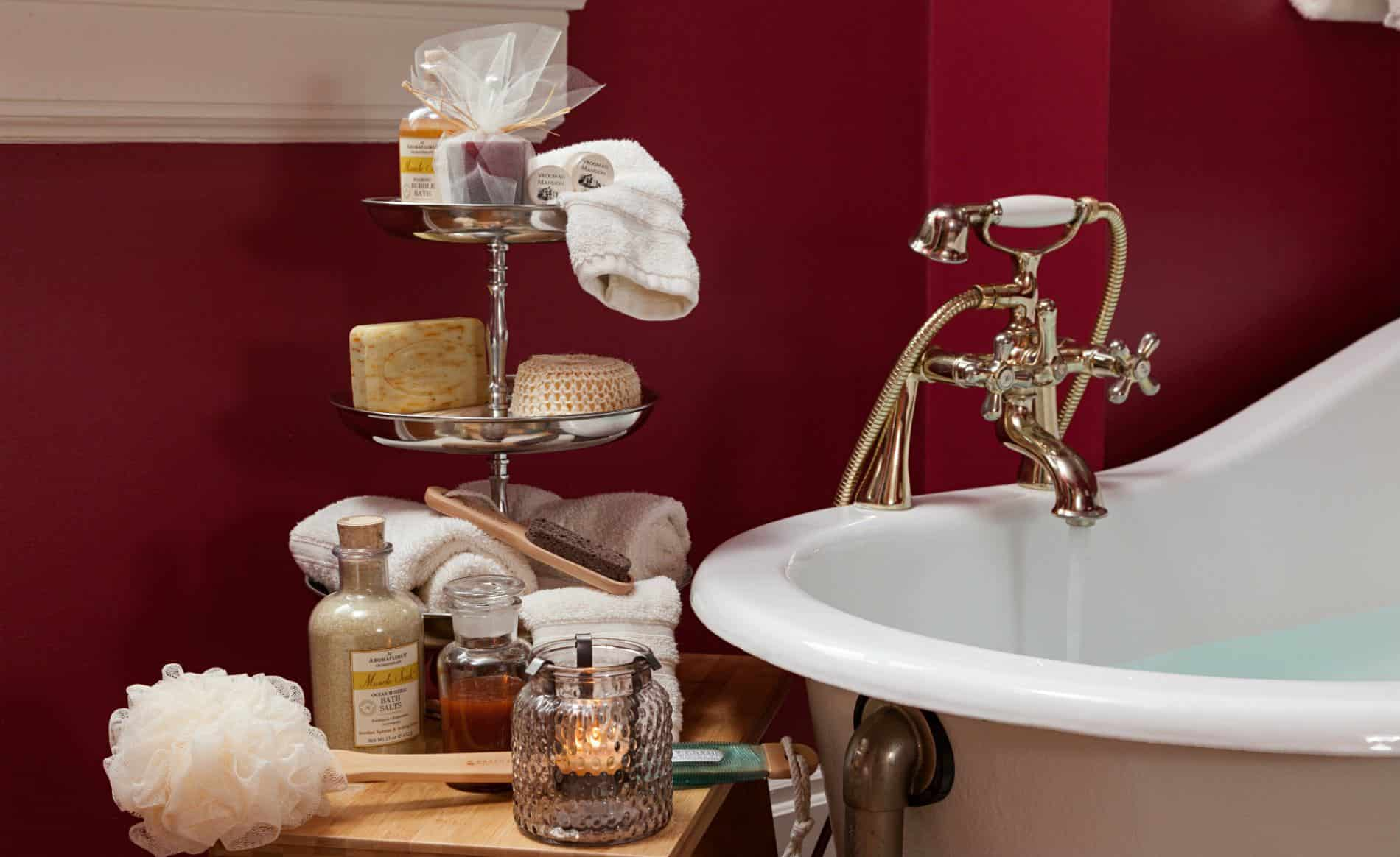 Close-up view of white clawfoot tub in red room and a wood stool topped with white towels and various toiletries