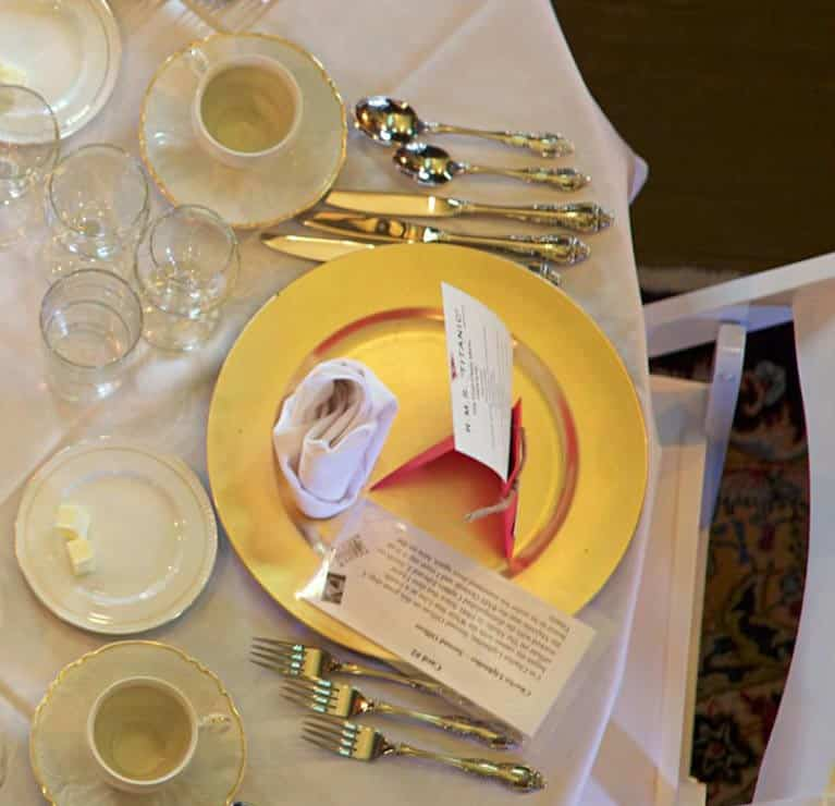 Titanic lunch gold plate dinner setting on white table cloth