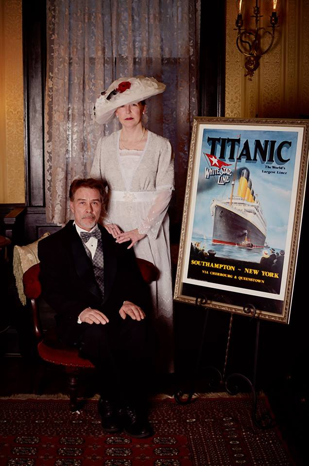 guests at titanic dinner at vroooman house. man sitting, woman standing behind him, hands on his shoulders, both in victorian clothes