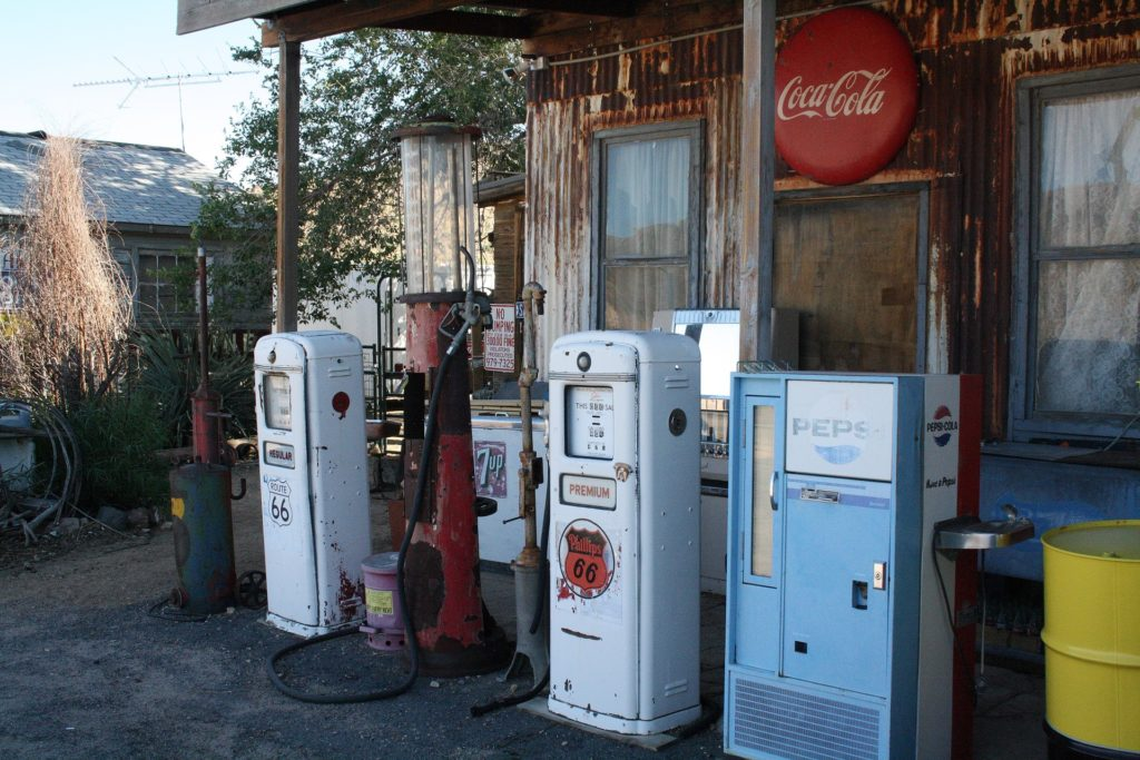 Old gas pumps and old soda machine in front of old building. Route 66