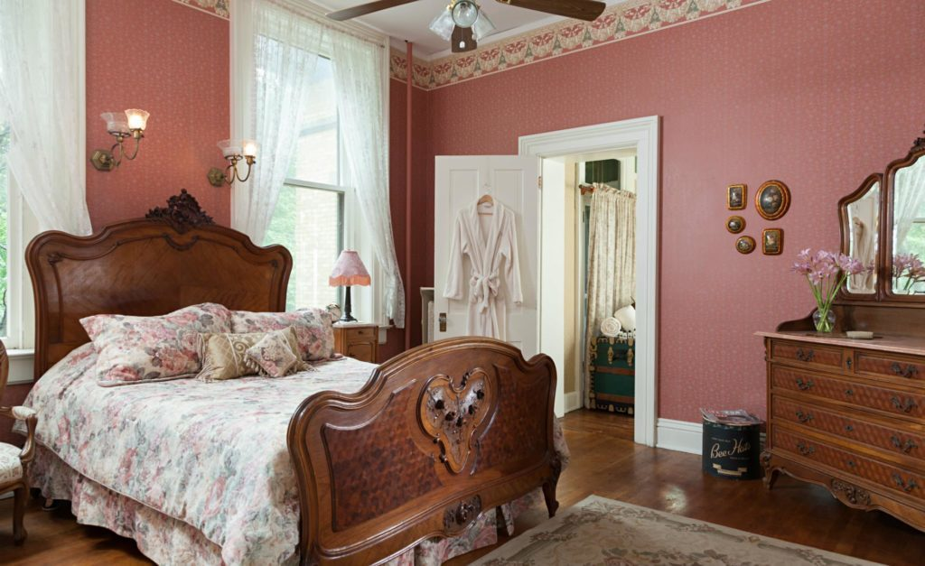 Antique, ornate wooden bed and matching chest. Rose-colored walls. Rose-patterned spread, pillows. Open bathroom door with white robe on door.