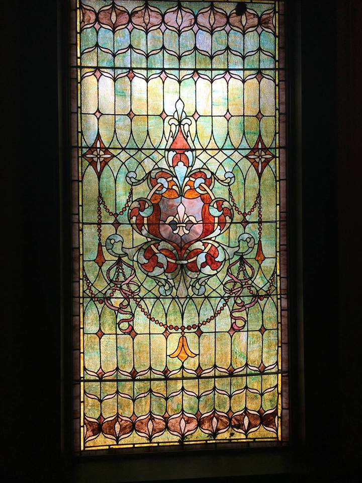 One stained glass window, green, yellow, pink
